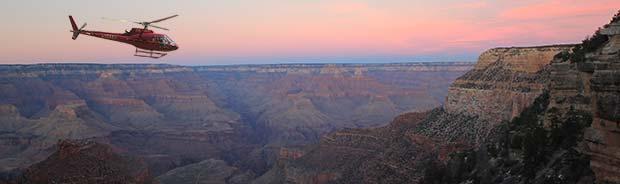 En helikopter som flyger i Grand Canyon vid solnedgång.